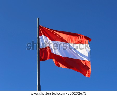 big Austrian flag waving in the blue cloudless sky