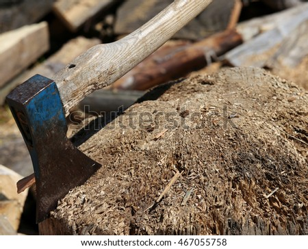 big ax of a woodcutter on the block of wood in the woodshed