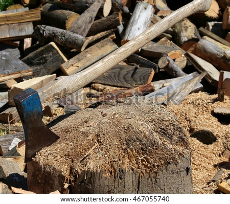 big ax of the woodcutter on the block of wood in the woodshed