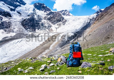 Big backpack on a background of mountains, in front of the pass and the glacier. Summer trekking hike in scenic Caucasus mountains, Bezengi region, Kabardino-Balkaria, Russia. - stock photo