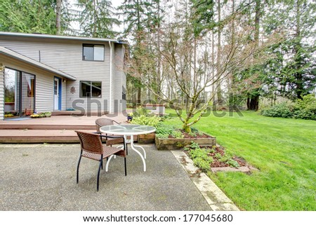 Big backyard with green lawn, wooden deck and concrete floor patio area with table and wicker chairs - stock photo