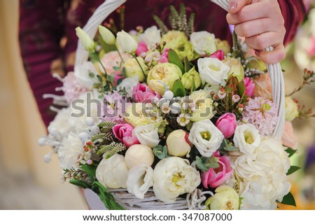 big basket with white light flowers bouquet  in hands