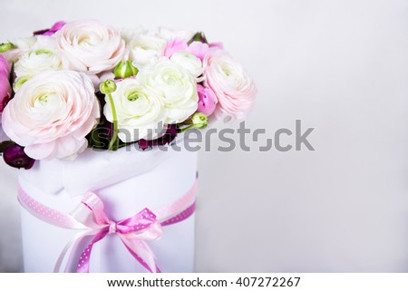 big beautiful bunch of summer flowers in round cardboard box over white background