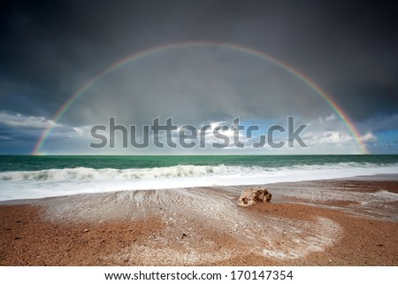 big beautiful rainbow over ocean waves after storm - stock photo