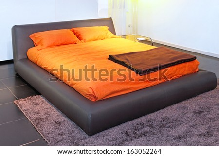 Big bed with orange cover in bedroom