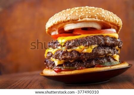 Big beef burger with three patties and cheese on plate , wood background - stock photo