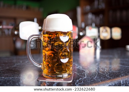 big Beer glass on a bar table. Closeup