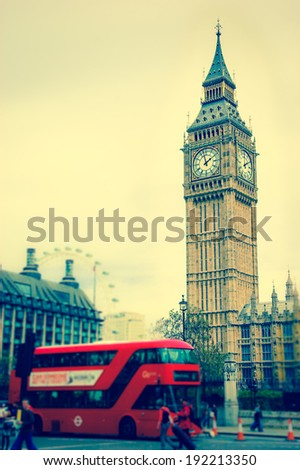Big Ben and blurred red double decker bus, tourists and London Eye. (London, UK). Aged photo. - stock photo
