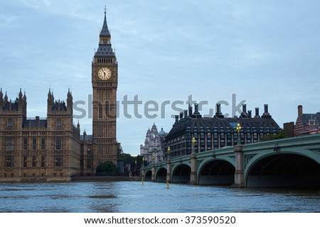 Big Ben and bridge, traffic on bridge at dusk in London, natural light and colors in the early cloudy morning in London, natural colors and lights - stock photo