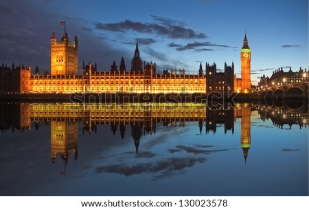 Big Ben and Houses of Parliament (Westminster Palace) in London reflected in River Thames at night - stock photo