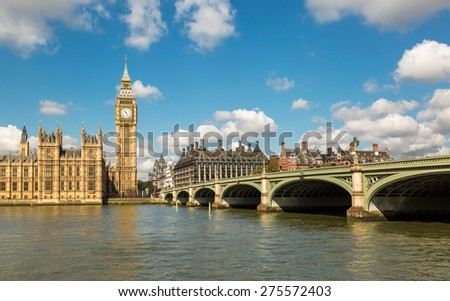 Big Ben and the Houses of Parliament in London with Westminster Bridge and the River Thames in the foreground against a blue sky with fluffy white clouds