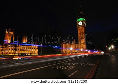 Big Ben and Westminster Abbey at night with police cars driving passed/ London Big Ben at night - stock photo