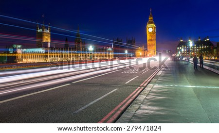 Big Ben clock tower, night shot with cars crossing the bridge. - stock photo
