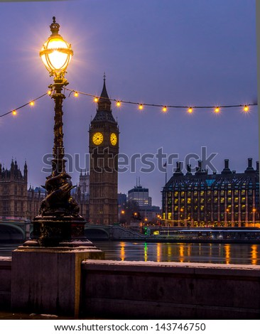 Big Ben in london with a lamp and the thames in the foreground