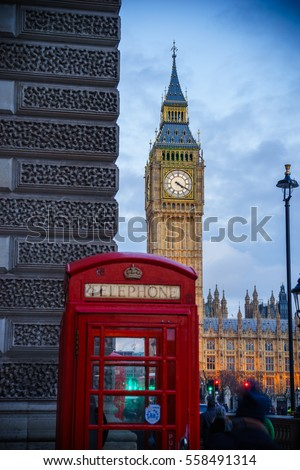 Big Ben, landmark of London at dusk with red telephone box in the foreground, selective focus