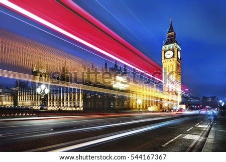 Big Ben, one of the most prominent symbols of both London and England, as shown at night along with the lights of the cars passing