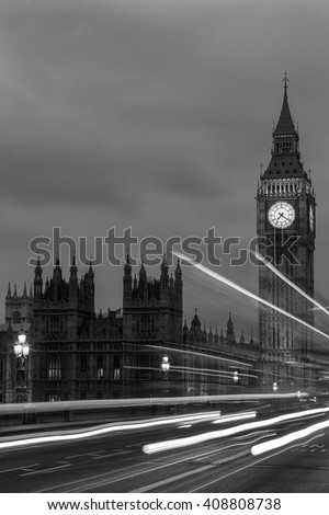 Big Ben, one of the most prominent symbols of both London and England, at night along with the lights of the passing buses in black and white - stock photo