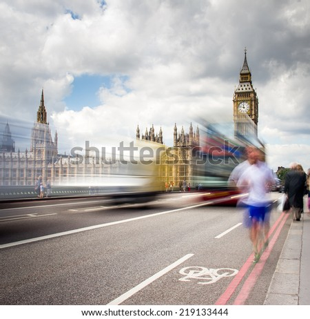 Big Ben with the Houses of Parliament and a red double-decker bus passing at dusk - stock photo