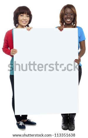 Big billboard presented by casual girls. Full length shots on white background - stock photo