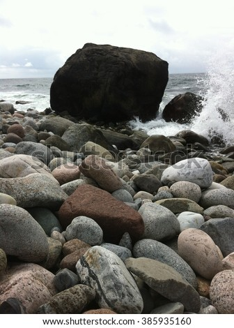 Big black rock in the water on stone beach in Norway - stock photo