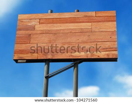 Big blank wooden billboard on blue sky background - stock photo