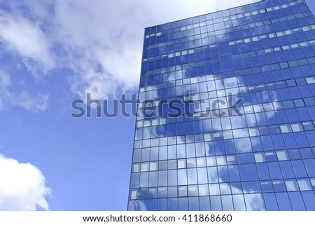 Big blue office building with sky reflection - stock photo