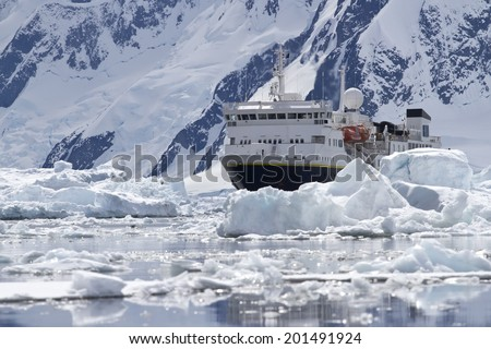 big blue tourist ship in the ice of the Antarctic mountains in the background of the Antarctic Peninsula - stock photo