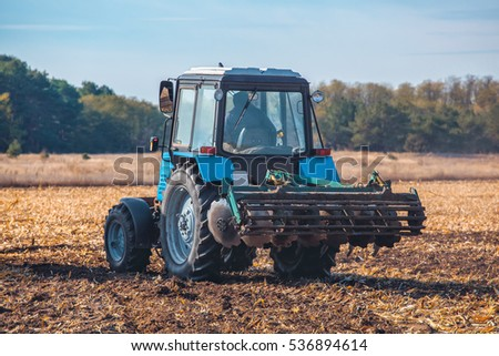 Big blue tractor plows the field and removes the remains of previously mown sunflower. Part of the cultivator, steel, round discs in a row close-up. Work agricultural machines. Harvest.