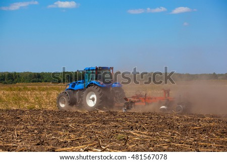 Big blue tractor plows the field and removes the remains of previously mown sunflower. Work agricultural machines.