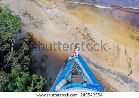 Big boat runs aground in sand beach in Rio Negro, Amazon, Brazil - stock photo
