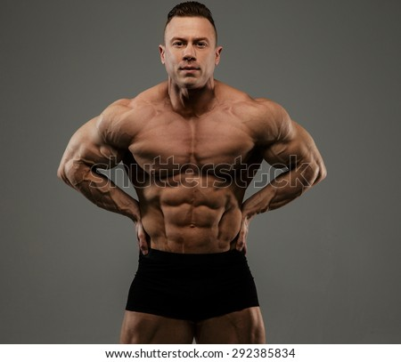 Big bodybuilder in black panties showing his muscles. Isolated on grey background. - stock photo