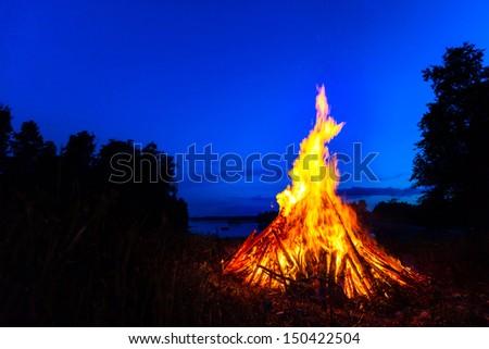 Big bonfire against blue night sky - stock photo