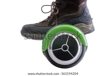 Big boot riding a modern motorised green hover board or self balancing scooter, the new trendy mode of transportation, isolated on white - stock photo