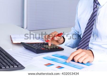 Big boss checks calculations on a calculator - stock photo