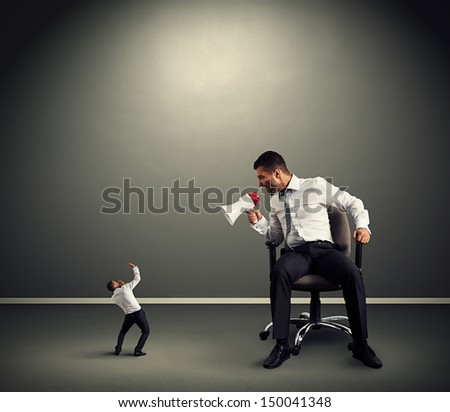 big boss with small businessman in grey room - stock photo