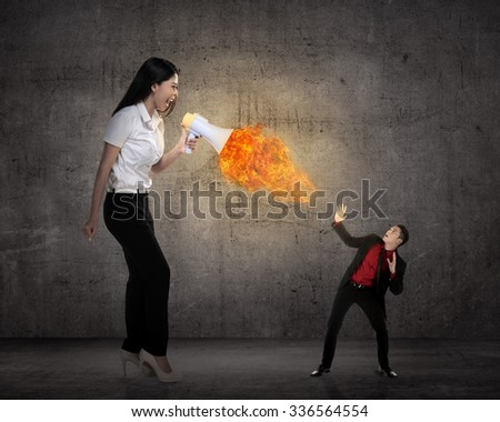 Big boss yelling to her employee with megaphone on fire. Work pressure concept - stock photo