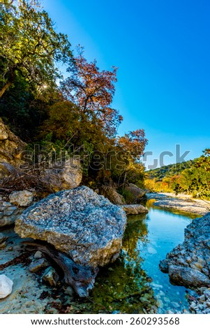 Big Boulders and Bright Beautiful Fall Foliage on Maple Trees on a little creek in Lost Maples State Park, Texas - stock photo