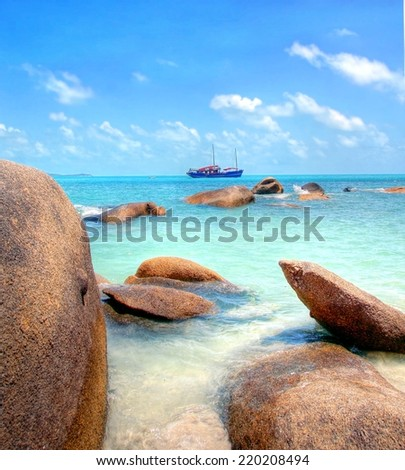 big boulders at the tropical coastline with turqiouse seawater - stock photo