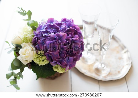 Big bouquet of fresh flowers, purple hydrangeas and white roses in a wicker basket, wine glasses and rustic wedding decor on a table, vintage style