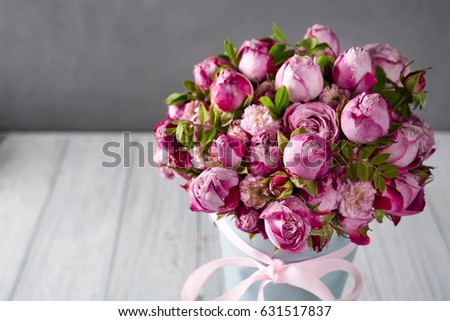 Big bouquet of roses in blue box on a wooden background