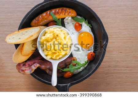 Big Breakfast or Brunch Set : Macaroni cheese, sausages, bacons, eggs, Garlic Breads served in sauce pan, selective focus, top view. Sided space for text (copy space) - stock photo