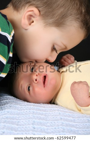 Big brother giving his baby brother a kiss - stock photo
