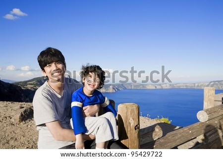 Big brother holding smiling disabled little boy with Oregon's famous Crater Lake in the background. Child has cerebral palsy - stock photo