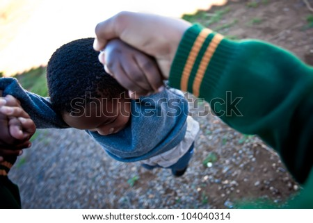 Big brother swinging his little brother around. - stock photo