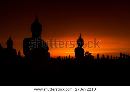 Big buddha statue in sunset background - stock photo