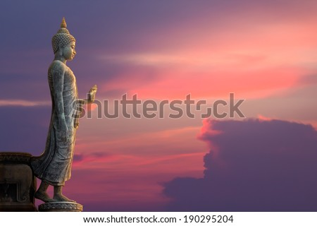 Big Buddha statue on sunset sky - stock photo