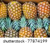 Big bunch of tropical pineapples in crate - stock photo