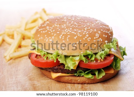 Big burger and chips on the table - stock photo