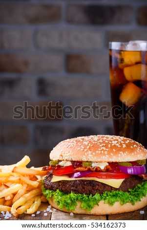 Big burger in classic american style with hot grilled patty with melted cheese on top, tomato, onion, sauces and french fries served with cold soft drink.