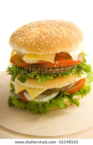 Big burger on a wooden plate isolated over white